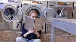 Eine junge Frau in einem Waschsalon halt einen Laptop wie ein aufgeklapptes Buch