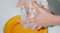 Eine Hand hält einen großen Eiswürfel über einem Teller (Foto: Moritz Jekat)