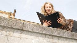 Eine Frau  liest in einem Laptop