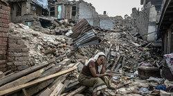 Nach dem schweren Erdbeben sitzt eine nepalesische Frau zwischen den Trümmern ihres Dorfes