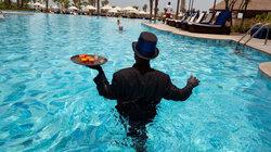 """Alex aus Ghana arbeitet als """"Pool Ambassador"""" im Ritz Carlton in Jumeirah.  Am Nachmittag serviert er Drinks am und im Pool"""