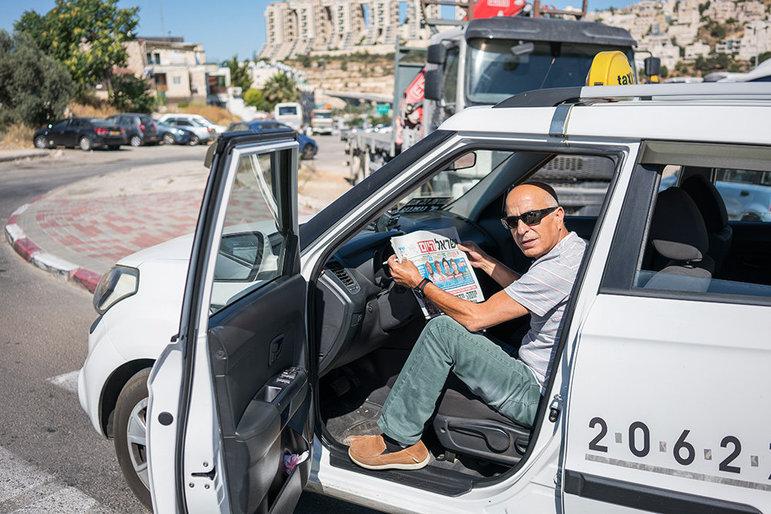 """Ein Mann liest """"Israel Hayon"""" auf einer Bank (Foto: Yaakov Israel)"""