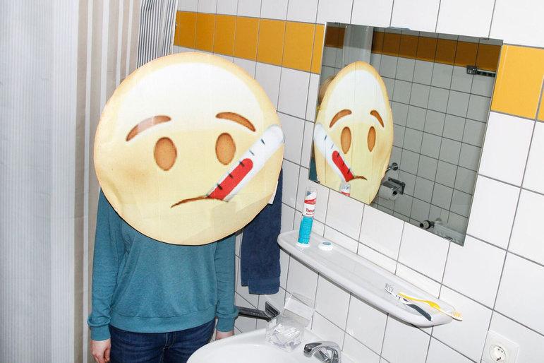 Emoji mit Fieberthermometer im Mund steht vor dem Badezimmerspiegel (Foto: Renke Brandt)
