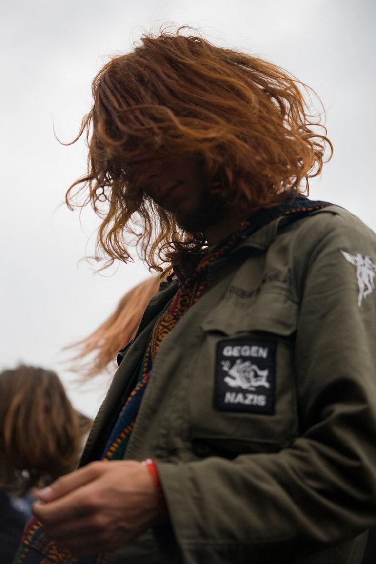 Festivalbesucherin mit Parka, das Gesicht vom langen Haar verdeckt