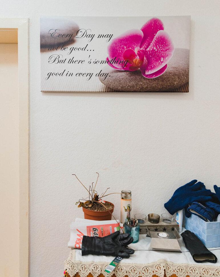 Die Wand einer Wohnung: Ein Bild einer pinken Blüte, verziert mit einer Lebensweisheit, darunter eine Ablage, auf der unter anderem Handschuhe, Teelichter und ein Werbeprospekt liegen   (Foto: Christian Protte)