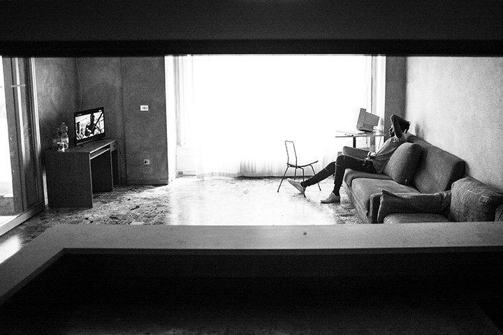 Malick guckt in der ehemaligen Lobby eines Hotels Fernsehen
