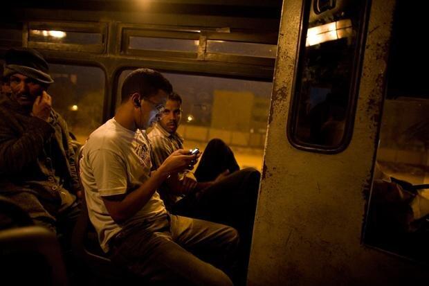 """Bevor es in Nordafrika losgeht, noch ein Blick aufs Telefon (Foto: Joël van Houdt, Serie """"Entering Europe"""")"""