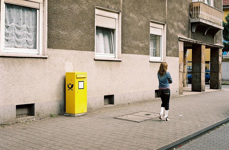 Frau läuft an einen Briefkasten vorbei (Foto: Christian Werner)