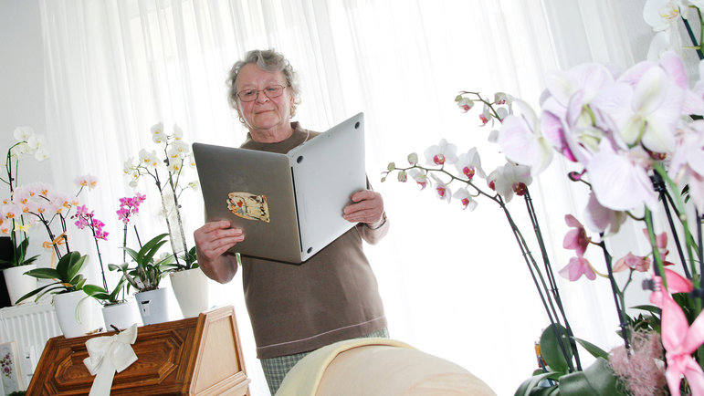 Von Orchideen umringte Frau hält Laptop wie ein Buch und liest darin