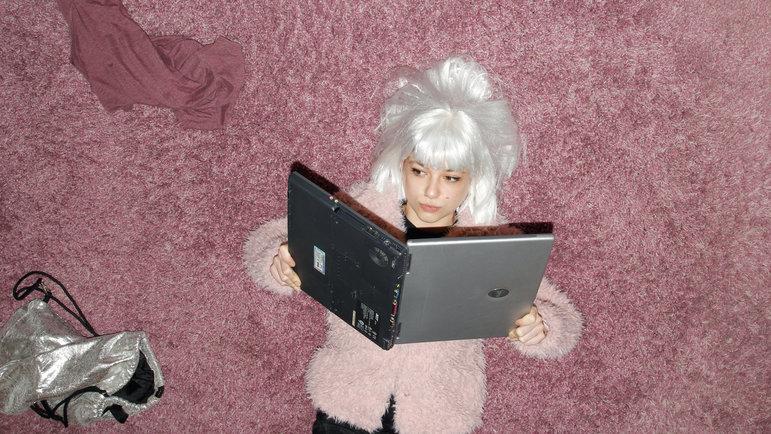 Mädchen mit Perücke liest im Laptop