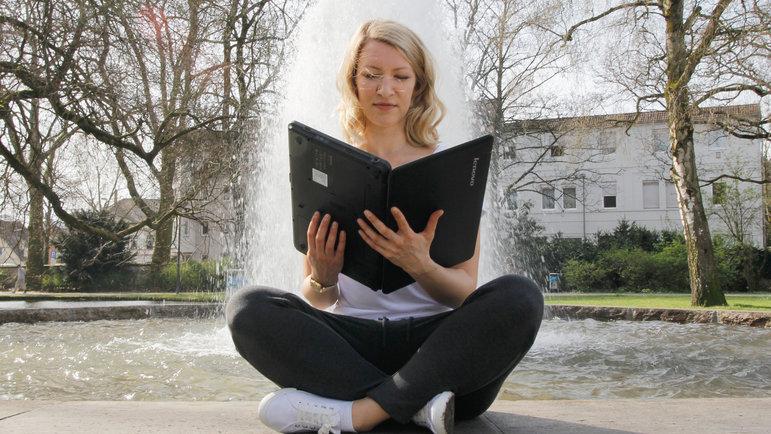 Eine Frau sitzt vor einem Springbrunnen und liest in einem aufgeklappten Laptop, als wäre es ein Buch