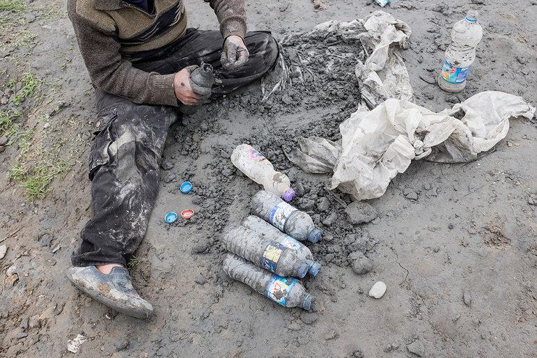 Ein Junge füllt Schlamm in Flaschen