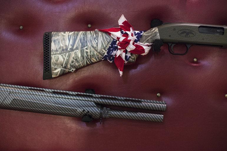 Zwei Gewehre liegen auf rotem Leder, eins mit einer USA-Flagge umwickelt