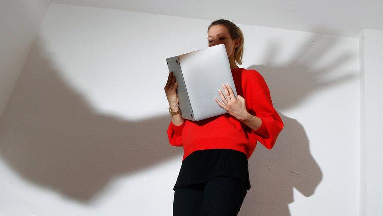 Eine Frau liest in einem Laptop wie in einem Buch