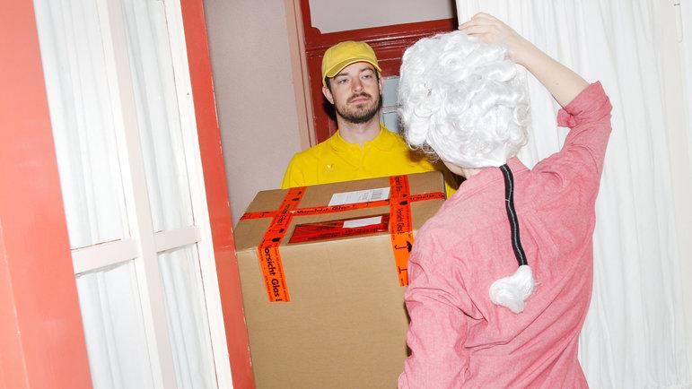 Frau mit Mozart-Perücke nimmt an der Haustür ein Paket an (Foto: Renke Brandt)