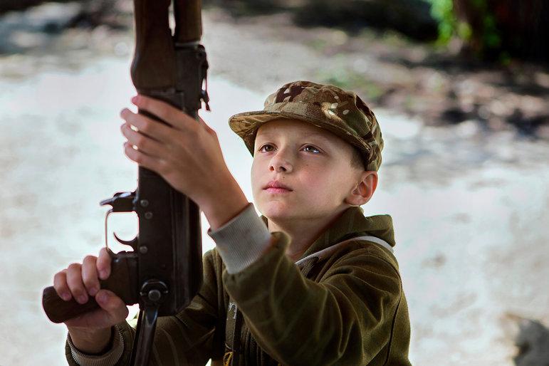 Ein Kind begutachtet seine Waffe