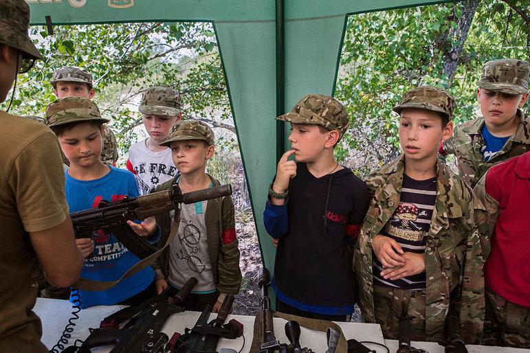 Kinder in Militärkleidung begutachten eine Kalaschnikow