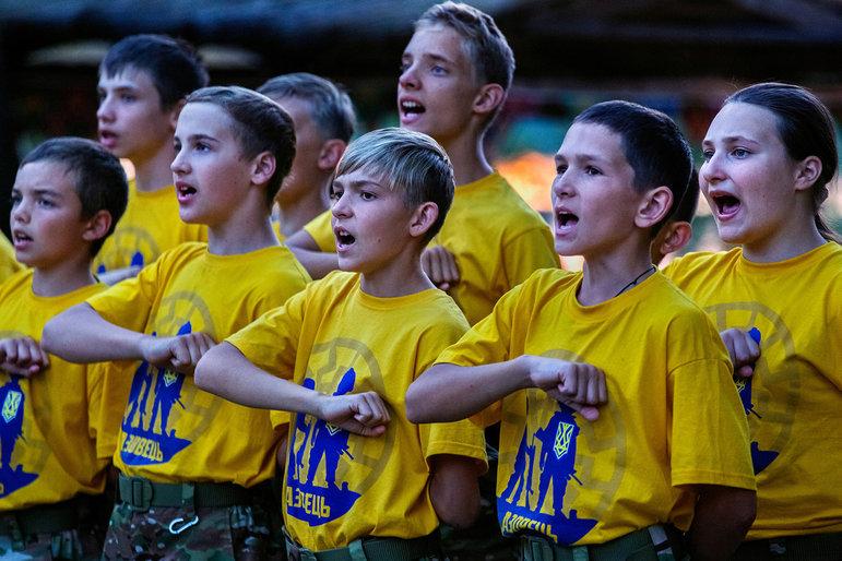 Kinder stehen mit auf der Brust geballten Fäusten in einer Reihe