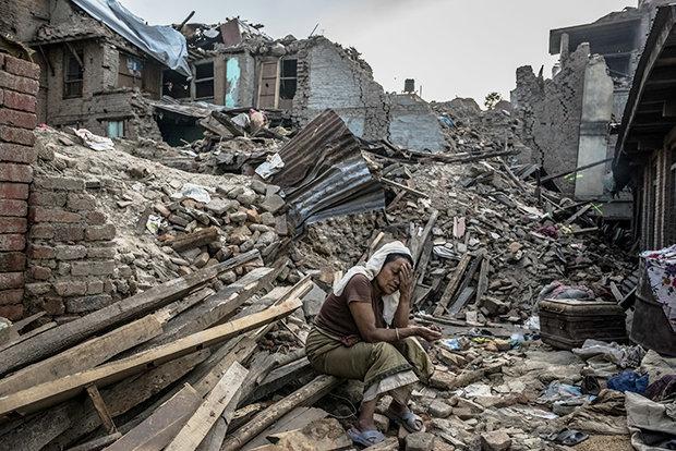 Nach dem schweren Erdbeben sitzt eine nepalesische Frau zwischen den Trümmern ihres Dorfes (Foto: DANIEL BEREHULAK/NYT/Redux/laif)