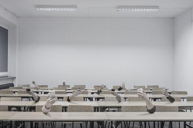 Körperlose Arme halten in einem Vorlesungsraum Smartphones in der Hand
