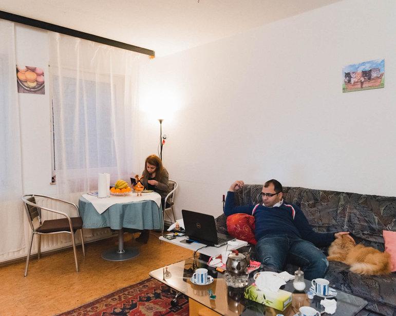 Ein Ehepaar in seinem Wohnzimmer: Aziz lümmelt mit dem Laptop auf der Couch, neben ihm liegt ein Kater. Lama sitzt am Tisch (Foto: Christian Protte)