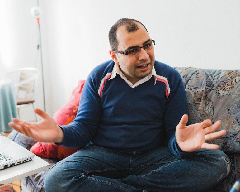 Der Syrer Aziz sitzt auf dem Sofa, erzählt und gestikuliert lebhaft (Foto: Christian Protte)