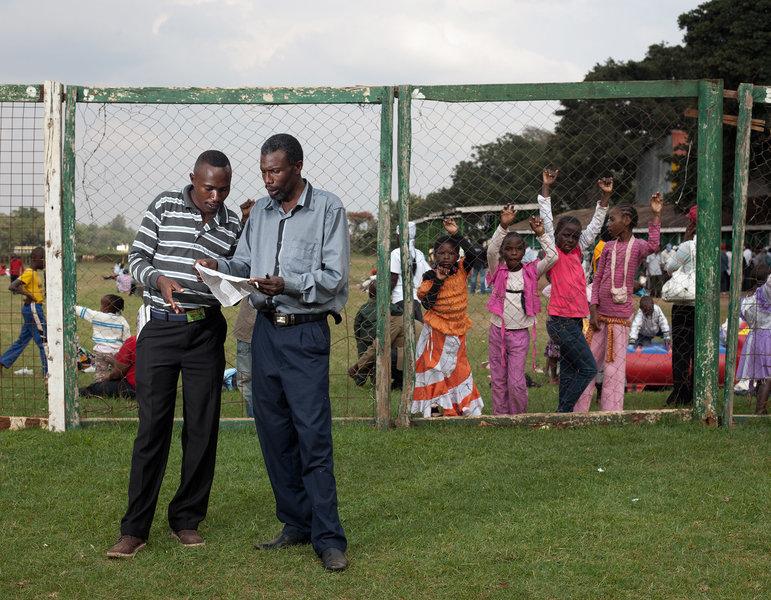 """Simon und Chris checken die Quoten beim Pferderennen im """"Ngong horse racecourse"""". Das Gelände dort ist in mehrere Bereiche aufgeteilt. Wo Simon und Chris sind, muss man Eintritt bezahlen, hinter dem Zaun auf den schlechteren Plätzen ist der Eintritt frei."""