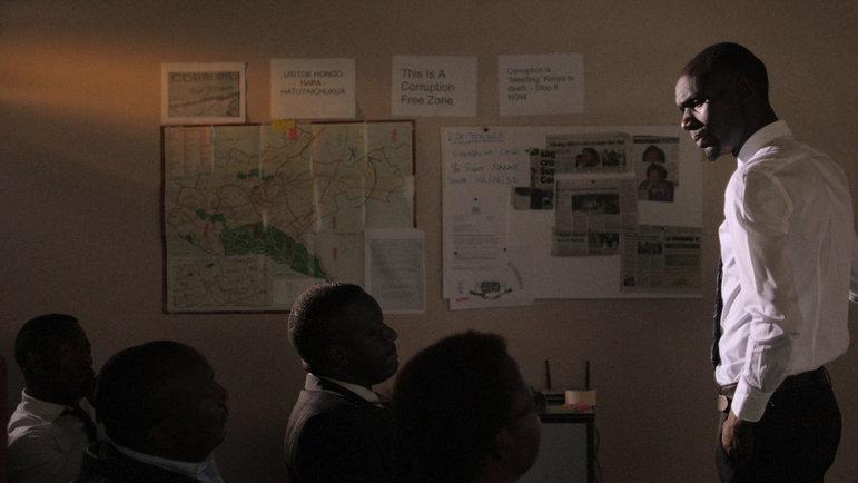 Szene aus der kenianischen Web-Serie Tuko Macho: Ein stehender Mann im weißen Hemd schaut zu einer Gruppe sitzender Menschen (THE NEST COLLECTIVE)