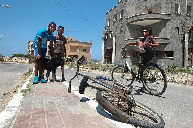 Jungs miot Rädern auf der Strasse in Jisr az-Zarqa (Foto: Eddie Gerald / Alamy Stock Photo)