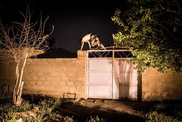 Ein junger Mann springt bei Nacht über ein Tor (Foto: Chris Grodotzki)