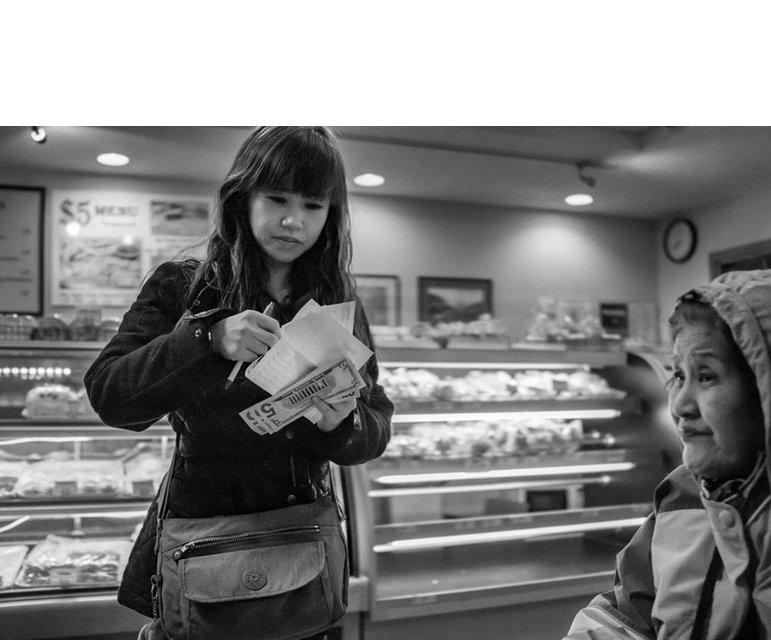 """Eine Reiseagentin von """"Lucky 9 Enterprises"""" verkauft die Tickets in einer Bäckerei."""