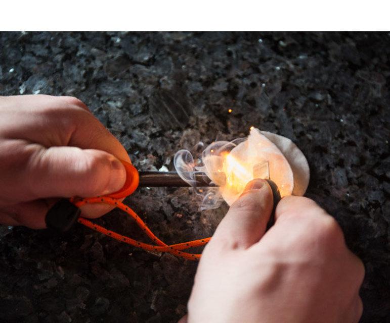 Mit einer Art Wetzstahl entfacht Bastian Blum Funken, die ein Wattepad schnell zum Brennen bringen – optimal, um mit Zunder und Holz schnell ein Feuer zu entfachen