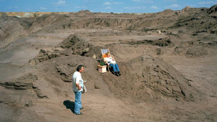 Mann und Frau mit Liegestuhl in Tagebau