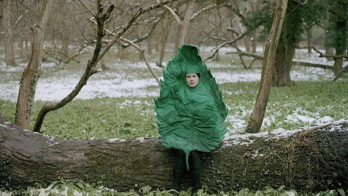 Eine als Blatt verkleidete Frau sitzt auf einem Baumstamm