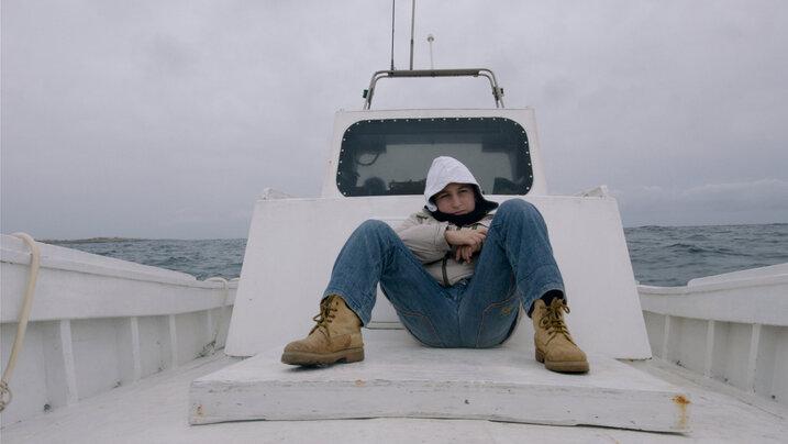 """Bild aus dem Film """"Fuoccoammare"""": Eine Person sitzt auf einem weißen Boot"""