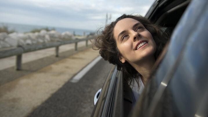 Die Protagonistin Sonia (Noémie Merlant) streckt den Kopf aus dem Autofenster und blickt Richtung Himmel