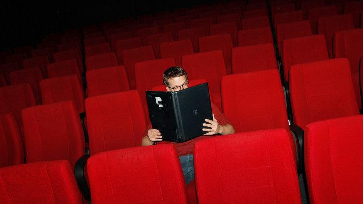 Ein Mann sitzt in einem Kinositz und liest im Laptop