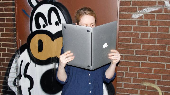 Ein Mädchen liest in einem Laptop, als wäre es ein Buch