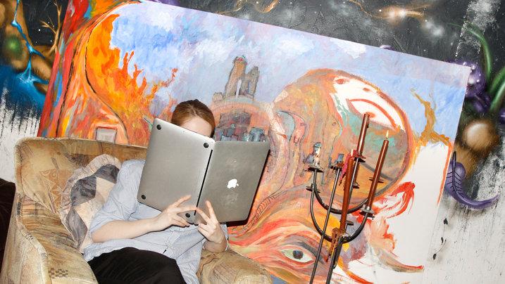 Mädchen auf einem Sessel liest im Laptop