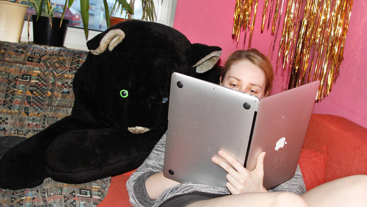 Frau hält aufgeklappten Laptop wie ein Buch und liest darin