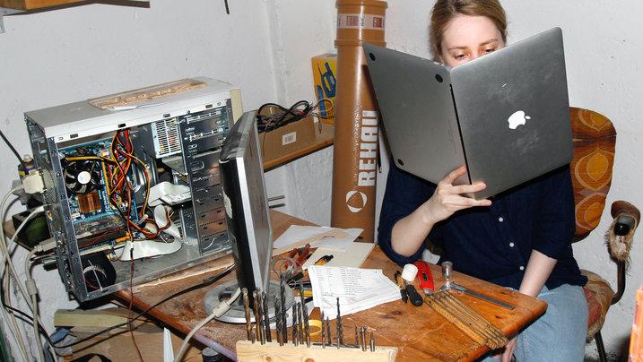 Frau liest in einem Laptop wie in einem Buch