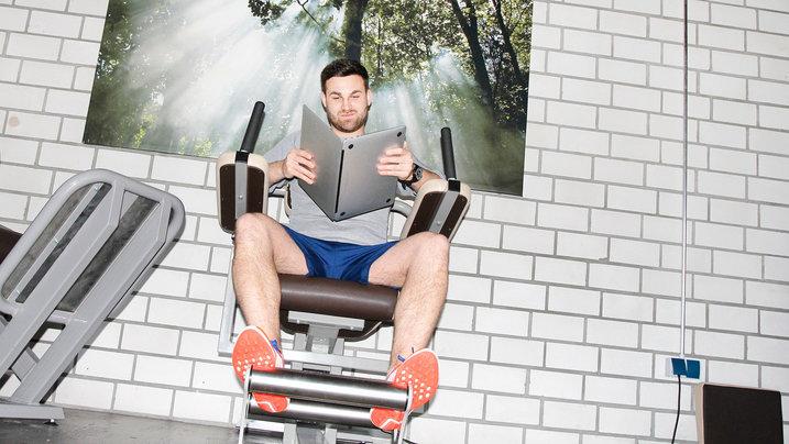 Mann auf Sportgerät liest in einem Laptop