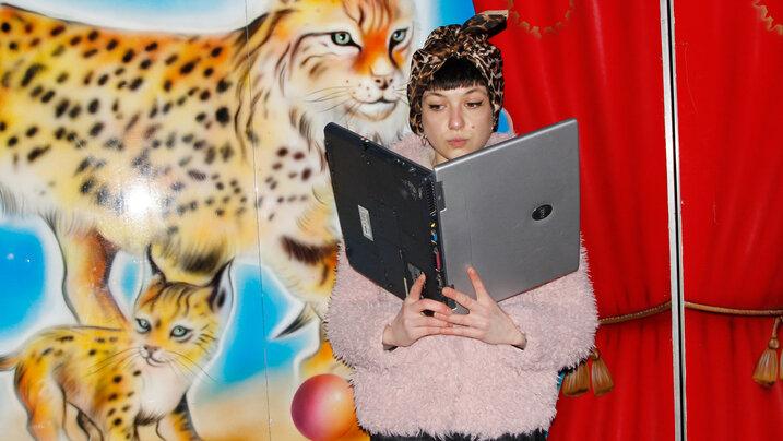 Junge Frau hält Laptop wie ein Buch und liest darin