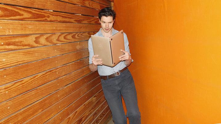 Junge Mann hält einen Laptop wie ein Buch, als würde sie darin lesen