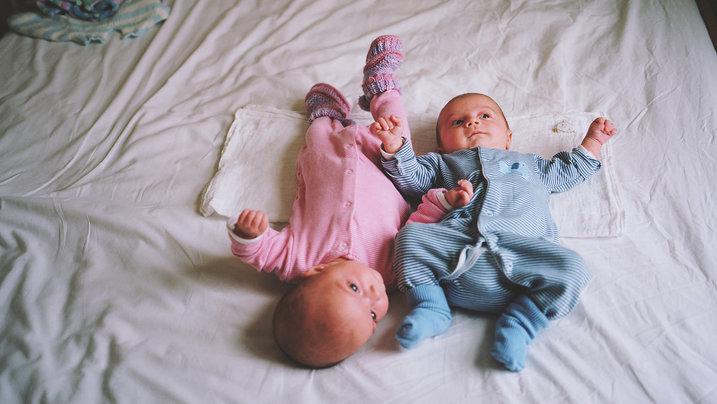 Zwei Babies liegen auf einem Bett; Foto: Kirsty Mackay/INSTITUTE