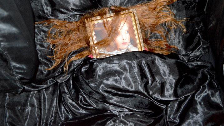 Rothaarige Frau mit einem Portrait auf dem Gesicht im Bett