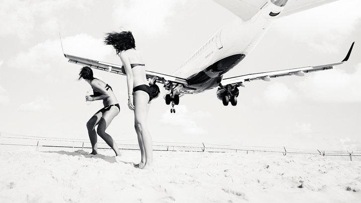 Tieffliegendes Flugzeug über zwei Frauen am Strand