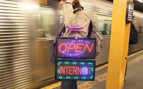 Der Künstler Aram Bartholl steht mit Leuchtschildern an der Ubahn