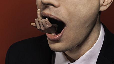 Einem Mann kommt eine Hand mit Stinkefinger aus dem Mund