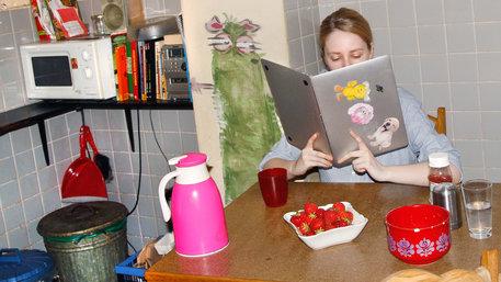 Eine Frau sitzt in der Küche und liest im Laptop